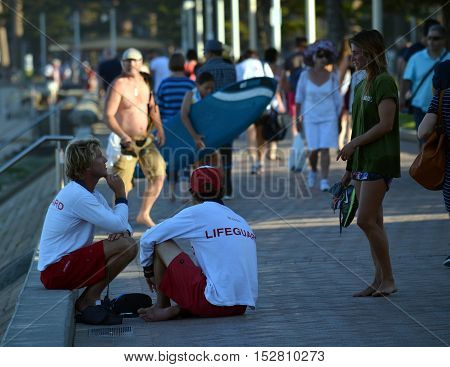Sydney Australia - April 14 2013. Lifeguards talking to a girl on Manly beach Marine Parade.
