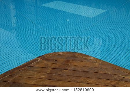 Swimming pool with old wooden flooring and blue water