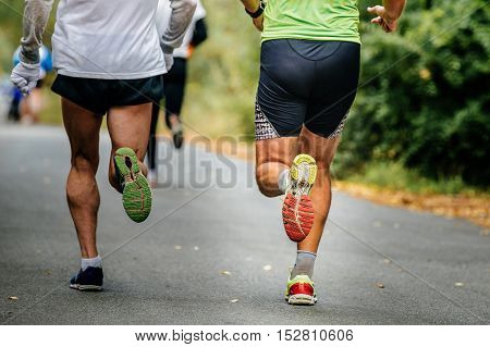 closeup of legs male runner running on road in autumn Park with fallen yellow leaves