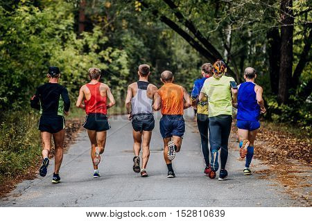 group of runners men run marathon in autumn Park with fallen yellow leaves