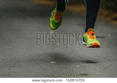 feet runner men compression socks and running shoes. flying over asphalt road with yellow leaves