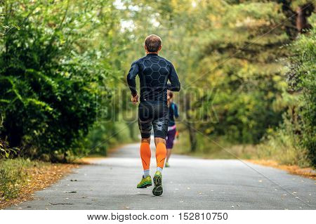 male runner in compression socks and clothes running down road in autumn forest