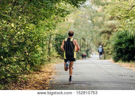 rear view male athlete runner running in autumn Park marathon