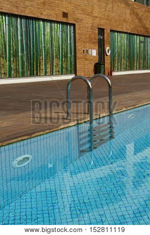 Swimming pool with old wooden flooring and blue water and bamboo wall