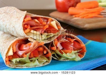 Almuerzo saludable, jamón, queso y verduras envuelven en una tortilla de trigo integral.