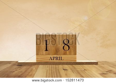 Cube shape calendar for April 18 on wooden surface with empty space for text.