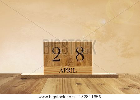 Cube shape calendar for April 28 on wooden surface with empty space for text.