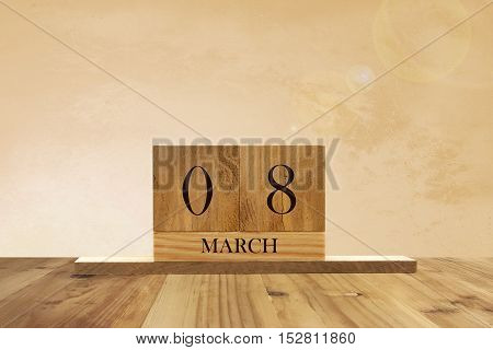Cube shape calendar for March 08 on wooden surface with empty space for text.
