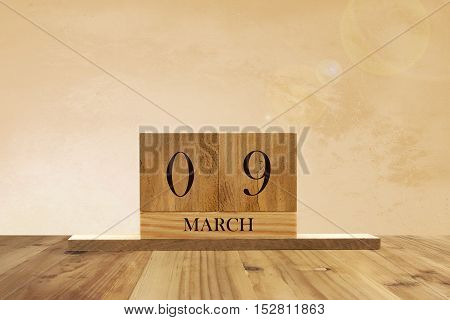 Cube shape calendar for March 09 on wooden surface with empty space for text.