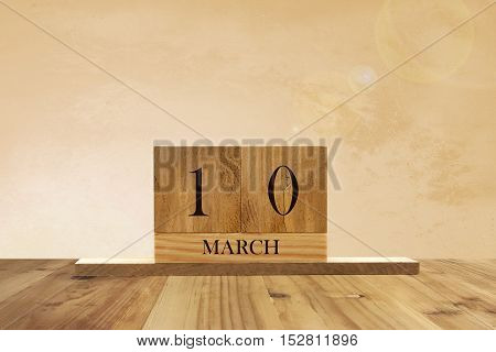 Cube shape calendar for March 10 on wooden surface with empty space for text.