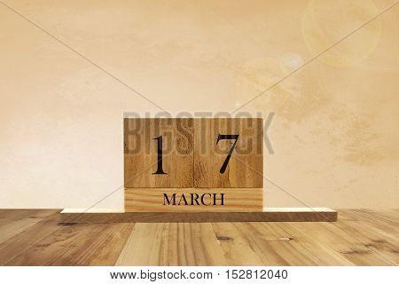 Cube shape calendar for March 17 on wooden surface with empty space for text.