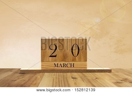 Cube shape calendar for March 20 on wooden surface with empty space for text.
