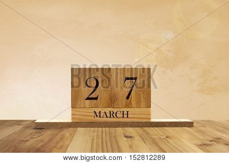 Cube shape calendar for March 27 on wooden surface with empty space for text.