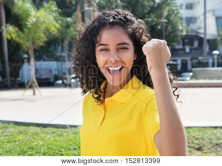 Cheering latin american girl with long dark hair outdoor in the summer in the city