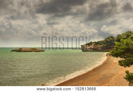 Summertime.Gargano coast: Baia di Campi beach,Vieste-(Apulia) ITALY-The pebbly beach is a picturesque bay sheltered the south by the Campi rock,framed by olive trees and pinewoods.Walk on the beach.