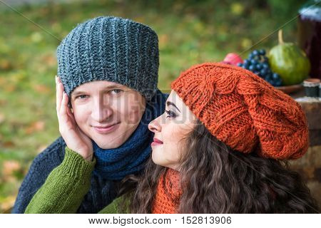 Closeup portrait of a stylish and romantic happy couple at fall in autumn garden