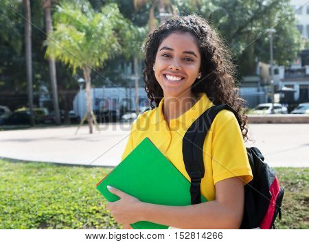 Laughing latin american female student with long dark hair outdoor in the summer in the city