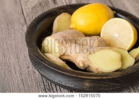 Lemon and ginger root in a wooden bowl on a gray wooden table.