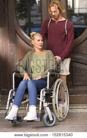 woman in wheelchair in front of an entrance and a young man helping her