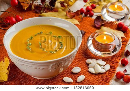 Pumpkin soup. Rustic background. Selective focus. White bowl. Orange napkin. The red berries of rose hips. Candles. Pumpkin seeds. Autumn yellow leaves. Autumn still-life.