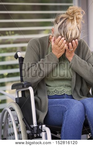blond woman in wheelchair outdoors is crying