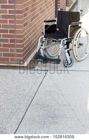 wheelchair standing by a brick wall on a sidewalk