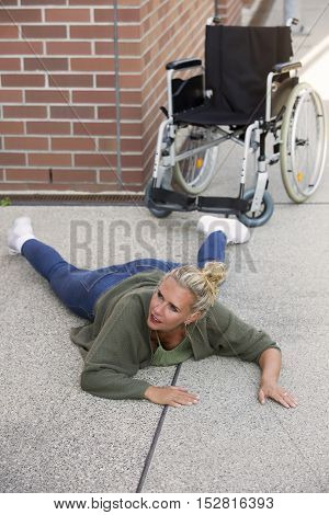 woman lying on floor on pavement next to a wheelchair