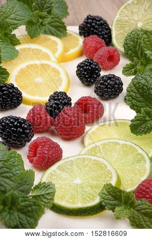 scattered blackberries and raspberries with lime and lemon slices mint twigs