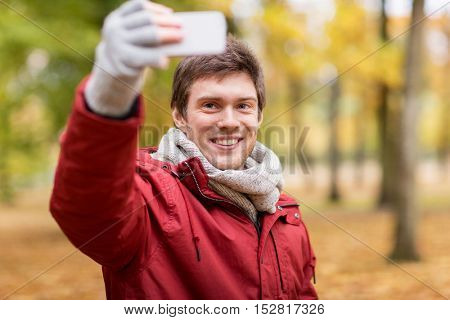 technology, season and people concept - happy smiling young man taking selfie by smartphone in autumn park