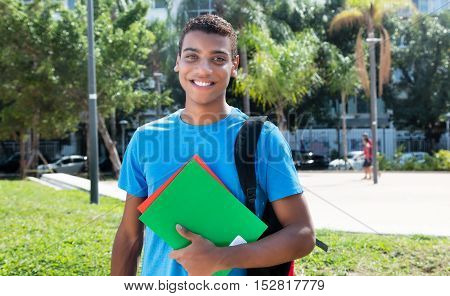 Funky latin american male student on campus of university in the summer