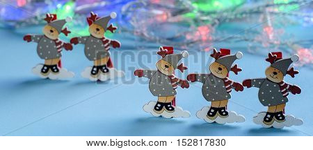 Five decorative figurines deer on a blue background. Decorations for the room and tree. Christmas and new year holidays. The twinkling lights of garlands.