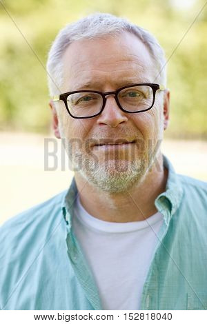 old age and people concept - close up of senior man in glasses outdoors