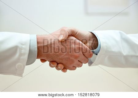 healthcare, profession, people and medicine concept - close up of doctors hands making handshake