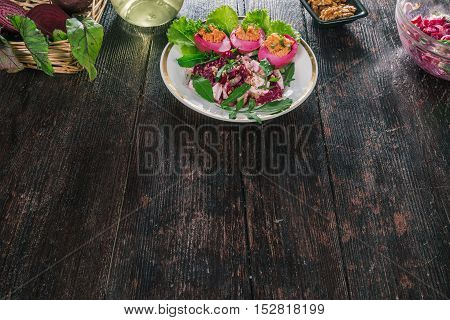Pickled bettroot eggs with spicy filling served with lettuce leaves and beet salad