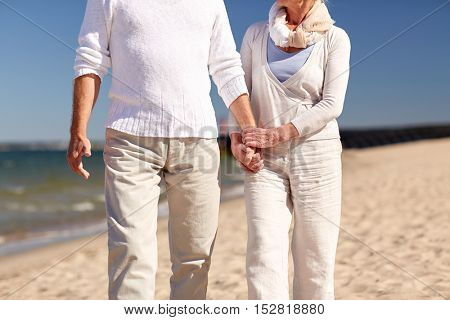 family, age, travel, tourism and people concept - close up of senior couple walking on summer beach