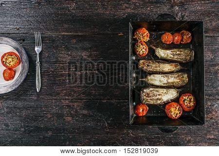 Eggplants and filled tomatoes baked on metal baking tray