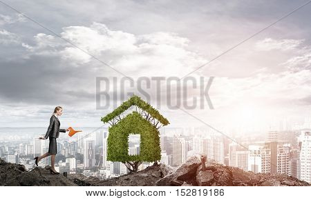 Young attractive businesswoman watering plant in ground with can against the backdrop of the city