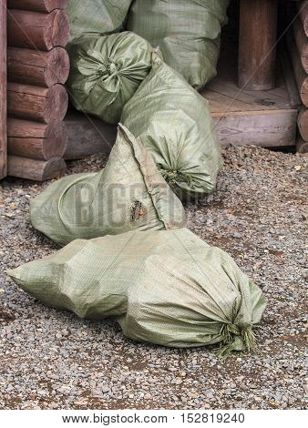 green bags of trash at the entrance in a wooden house