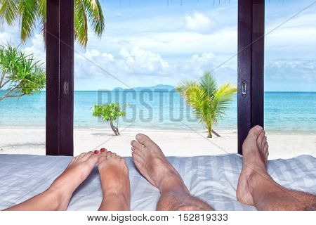 Close up view of man's and woman's legs on the bed in tropical resort