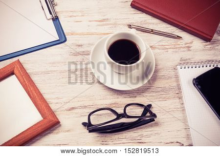 Still life photo of tablet notepad coffee glasses on wooden table