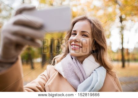 season, technology and people concept - beautiful young happy woman taking selfie with smartphone in autumn park