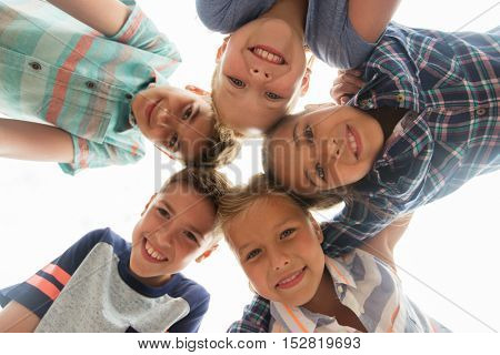 childhood, leisure, friendship and people concept - group of smiling happy children faces in circle