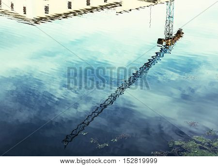 Crane is mirroring in blue water. Industrial scene. Retro photo filter.