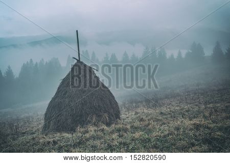 Amazing rural scene on autumn valley. Alone haystack on a foreground. Carpathians, Ukraine, Europe, toned like Instagram filter