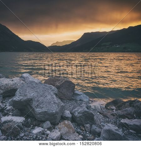 Beautiful view of the lake Resia. Dramatic sky and colorful sunset. Alps, Italy, Europe, toned like Instagram filter
