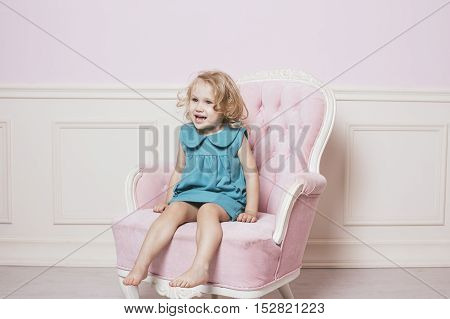 Little beautiful and happy baby girl sitting on a beautiful vintage pink chair in a retro dress as a doll