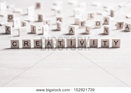 wooden elements with letter on wooden table spelling word creativity