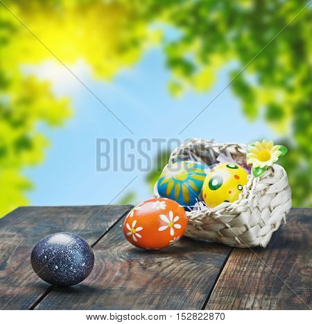 Painted Easter eggs in a basket on the table with space for text