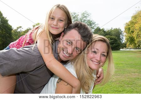 Parents Giving Piggyback Ride To The Daughter
