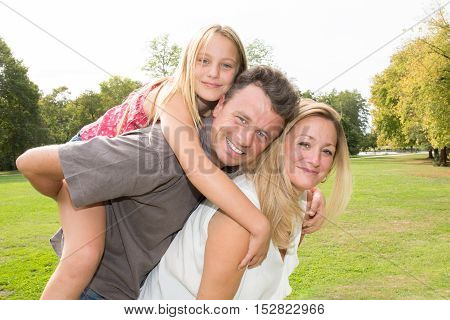 Father And Mother Giving Piggyback Ride To The Daughter